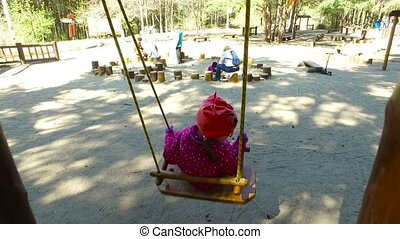 Child girl swinging on a swing in the park. The girl is happy and smiling. Good spring weather. Sunny day.