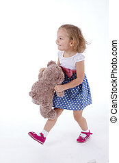 little girl carries a teddy bear, goes with him