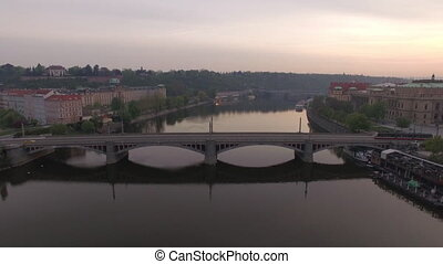 Flying over Manes Bridge across Vltava river in Prague -...