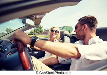 happy man and woman driving in cabriolet car - road trip,...