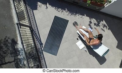 Young Man Sunbathing and Putting on Sunscreen Cream -...