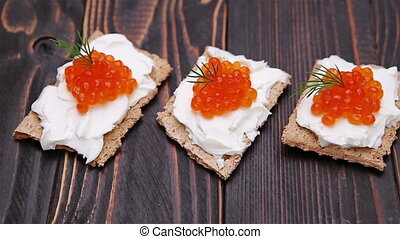 crackers with cream cheese and red caviar close-up on wooden...