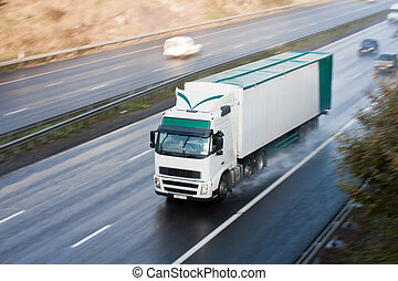 White and green truck blurred motion on wet motorway