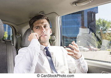 Busy young businessman in a taxi
