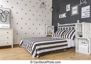 Functionality of black and white - Shot of a bed in a modern...