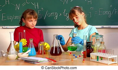 Children in chemistry class. - Children looks into flask in...