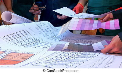 Hands of builder people work on drawings at construction site.