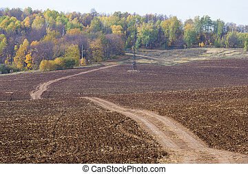 Autumn, the road is unpaved, freshly plowed field, a hill...