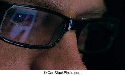 Eyes of serious young man in black rim glasses using his...