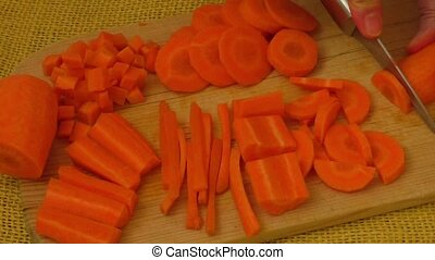 Slicing carrot on cutting board - Close up on woman's hand...