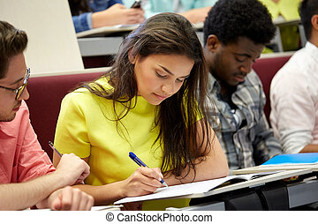 group of international students writing at lecture