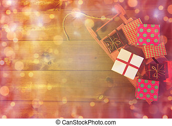 close up of christmas gift boxes on wooden sleigh -...