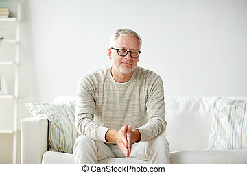 smiling senior man in glasses sitting on sofa - old age,...