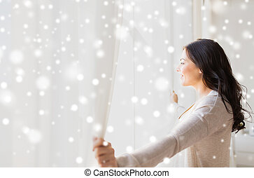 close up of woman opening window curtains - people, winter,...
