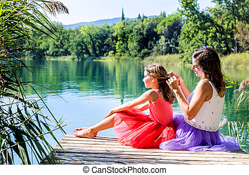 Girls relaxing next to lake. - Portrait of two girls...