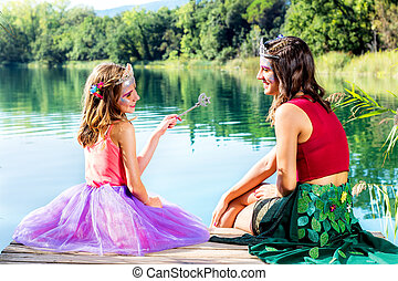 Two girls telling fairy tails at lake.