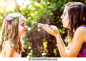 Fairy blowing magic powders to girl.