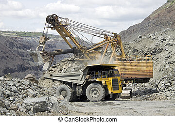 Mining - Loading the iron ore into heavy dump truck at the...