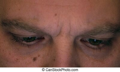 Eyes of serious frowning caucasian man using his tablet...