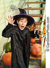 scare on Halloween - A boy in a costume of wizard with his...