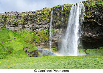 One of the hundreds of wter falls in Iceland -...