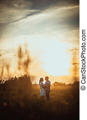 love story man and woman on the background of haystacks sun...