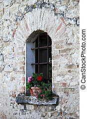 Medieval window with flowers pots