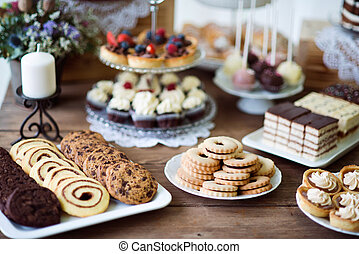 Table with various cookies, tarts, cakes, cupcakes and...