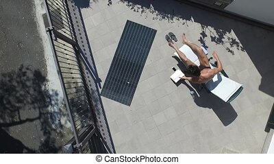 Young Man Sunbathing and Writing on Notepad - Shirtless...
