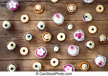 Table with various cupcakes, tarts and cookies. Flat lay. -...