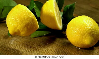 Lemons with leaves on wooden boards. - Falling lemons with...