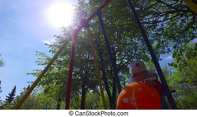 Girl child swinging on a swing. Girl holding a large orange...