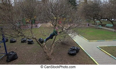 Flying over child on the tree in house yard - Aerial view of...