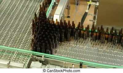 Empty brown bottles in a line in factory