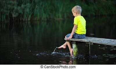 boy sitting on bridge at pool - cute boy sitting on bridge...
