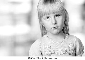 serious blond little girl with blue eyes looking sadly