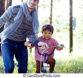 father learning his son to ride on bicycle outside in park
