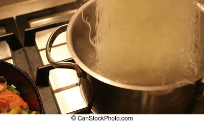 Rice noodles in boiling water - Putting rice noodles into...