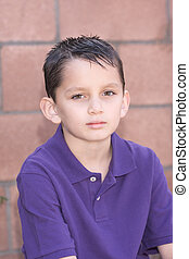 Portrait young biracial boy with short hair by brick wall -...