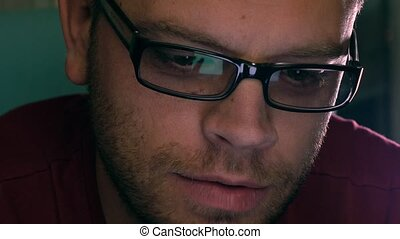 Serious handsome young man in black rim glasses using his...