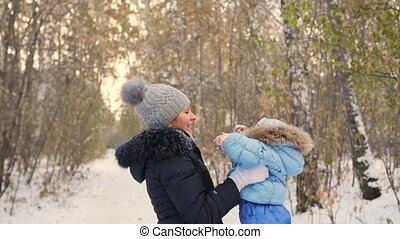 mother playing with baby in winter Park. Spinning