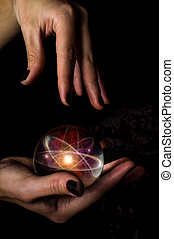 Crystal Ball Atom - Female hands hold crystal ball with atom...