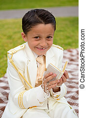 Young First Communion boy smiling with prayer book and rosary