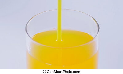 Close up of drinking orange soda with a straw at white background