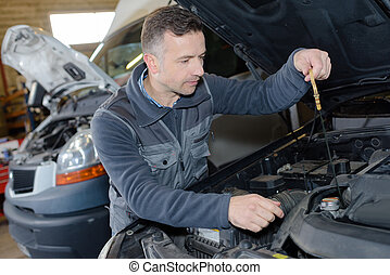 car mechanic replacing oil on engine in garage