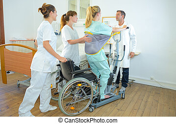 Medical staff helping woman to standing