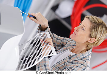 young woman fixing air conditioner in house