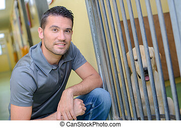 Man next to dog in kennel