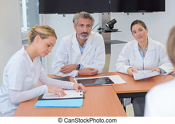 Medics sat around table in discussion