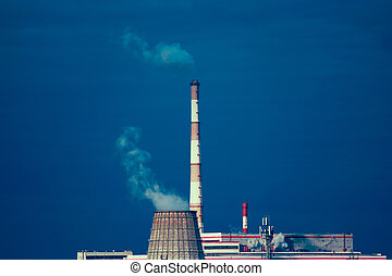 Power plant with two smoking chimney in front of blue sky. Cooling tower of power-plant against the blue sky
